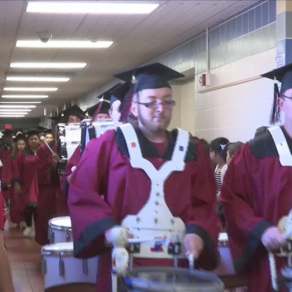 EHS graduating seniors walk through elementary schools in caps and gowns